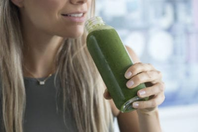 woman with Wheatgrass drink