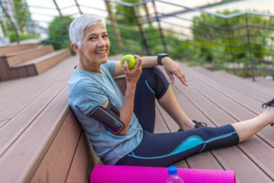 Mature athletic woman eating an apple after sports training